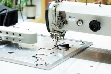 Machine sews parts of shoes, close-up