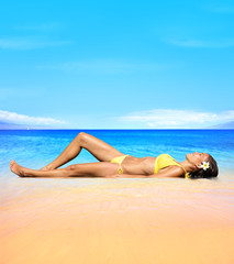 Beach travel Sunbathing woman relaxing under sun