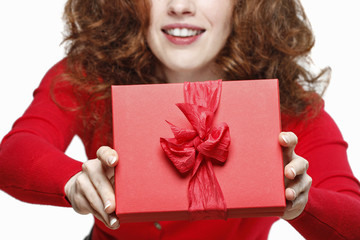 Woman holding red present box with big bow