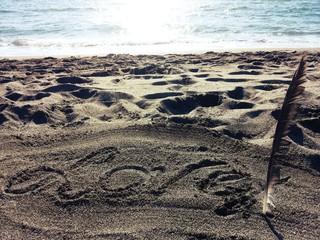 Scritta fatta con una piuma sulla sabbia