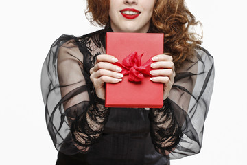 Glamorous woman holding red present box with big bow