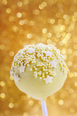 Pink and yellow cake pops decorated with sprinkles.