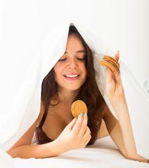 Woman eating cookies in bed