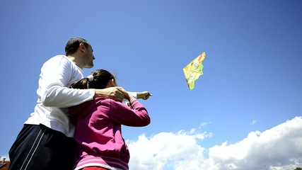 Young family flies kite together, wide angle