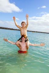 boys having fun in the clear sea