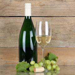 Weißwein in Flasche und Weinglas vor Holz