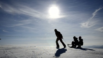 Father and kids silhouettes having fun on the snow with a sledge