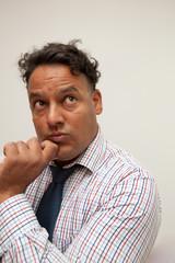 Ein gebräunter mann mit Hemd und Krawatte denkt nach