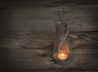 Lamp-lantern with a candle on wooden background