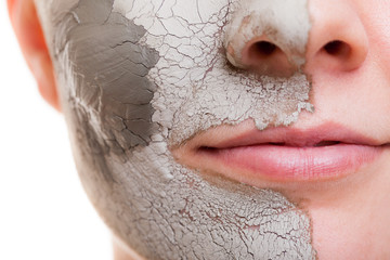 Skin care. Woman applying clay mask on face. Spa.