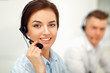 Businesswoman with headset smiling at camera in call center - 70137156