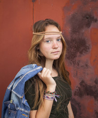 Young girl dressed in hippie style,of burgundy metal wall.