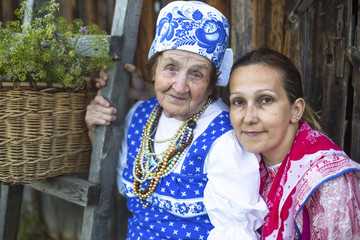 Grandmother and her daughter in ethnic clothes outdoor.