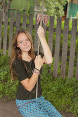 Teen girl swinging on a rope swing in the countryside.