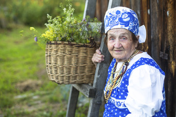 Slavic happy elderly woman in ethnic clothes outdoor.