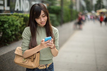 Young Asian woman in city texting message on cellphone