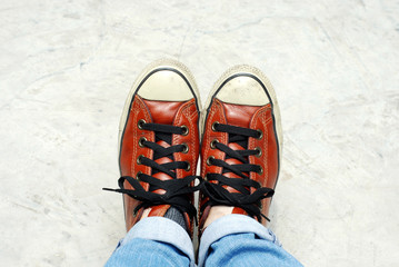 Feet in sneaker on concrete floor.