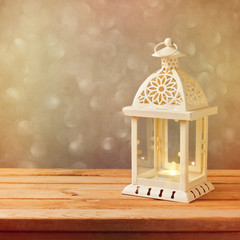 Decorative lantern with glowing candle on wooden table