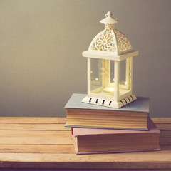 Lantern with candle and vintage books on wooden table