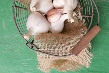 Garlic in basket on color wooden background