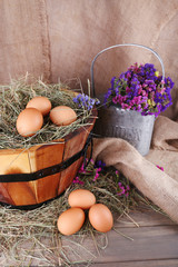 Big round basket with dried grass and fresh eggs