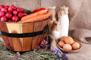 Big round basket with dried grass, vegetables, milk and fresh