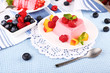 Cakes with fruit and berries on plate on lace napkin