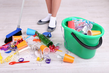 Woman cleaning grey wooden floor from mess