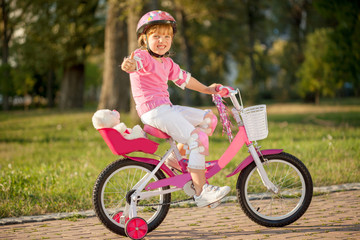 Portrait of a playful funny girl in a pink safety helmet on her