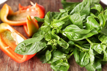 Green fresh basil and sliced bell pepper  on wooden background