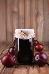 Tasty plum jam in jar and plums on wooden table close-up