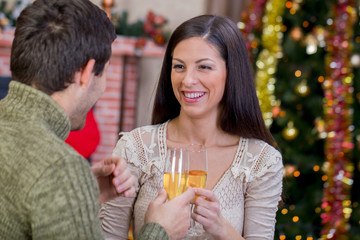 couple holding glasses with champagne and celebrate Christmas ni