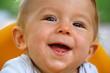 canvas print picture - Lachendes Baby (Junge) mit erstem Zahn