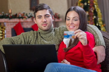 young happy  Couple Using Credit Card to E-Shop on christmas nig