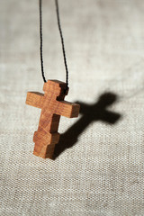 Wooden cross with deep shadow on wooden background