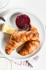 Croissants with butter and a glass of milk on a plate