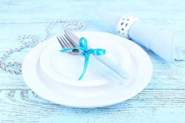 White plates, fork, knife, napkin and Christmas decoration