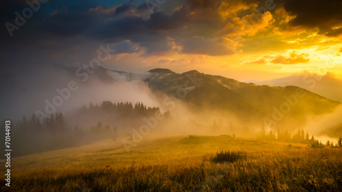 Foto op Canvas Heuvel Amazing mountain landscape with fog and a haystack