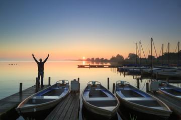 Man enjoying the sunrise on a jetty in a marina.