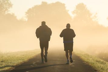 Two men running in the morning fog.