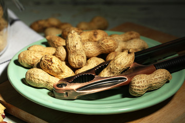 Peanuts and nutcracker on plate, on wooden background