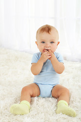 Cute baby boy on carpet in room