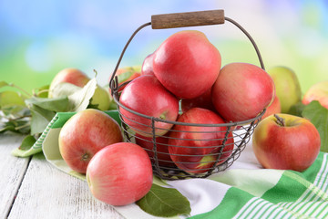 Sweet apples in wooden basket on table on bright background
