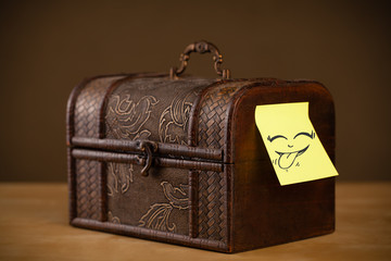 Post-it note with smiley face sticked on jewelry box