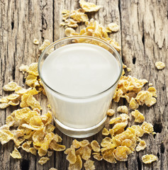Milk and conflake on table wooden background