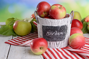 Sweet apples in basket on table on bright background