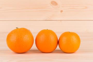 Three fresh oranges on wood table.
