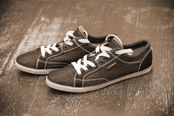 Black shoes with white laces on the vintage background, sepia