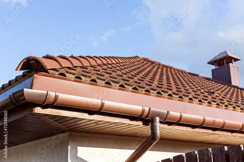 Red tiled roof with gutter and chimney - 70148160