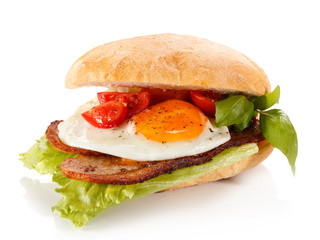 Breakfast - breadroll, fried egg, bacon and vegetables